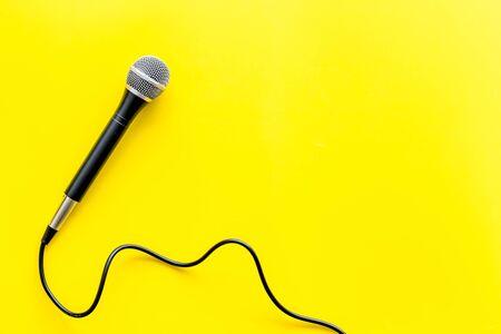 TV news concept. Microphone on yellow background top-down. 版權商用圖片