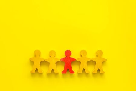 Leadership concept. People cutuots - red figure against others on yellow background top-down copy space