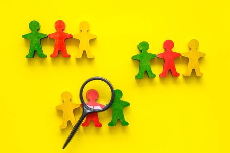 Tolerance concept. Social research. eople cutouts under magnifier on yellow background top-down copy space Stock Photo