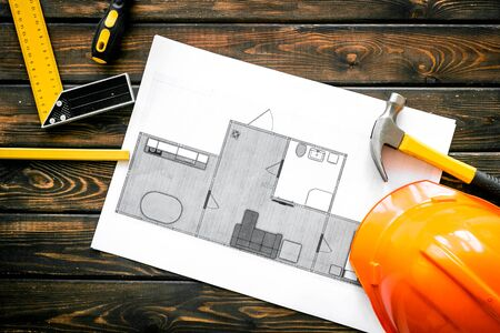 House building plan. Blueprints, instruments, helmet on dark wooden background top-down.