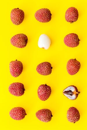 Lychee fruits pattern on yellow background flat lay top-down
