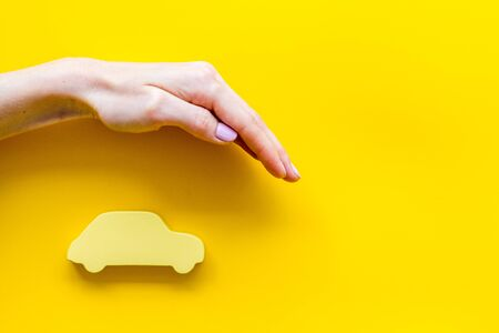 Car insurance. Hand defends automobile cutout on yellow background top-down copy space Imagens