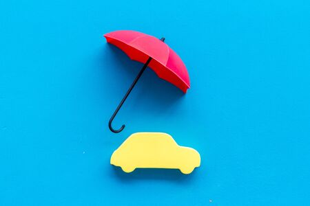 Car protection concept. Automobile cutout defended by umbrella on blue background top-down copy space