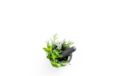 Herbs in ceramic mortar with pestle on white backgroud top-down. Archivio Fotografico