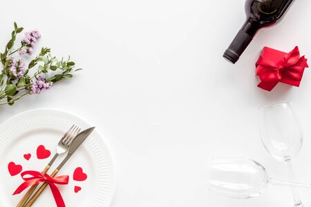 Romantic dinner on Valentines Day. Wine, plate, present box on white background top-down copy space