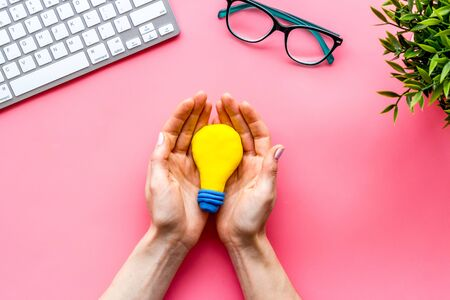 Idea concept. Light bulb in hands on pink office desk top-down
