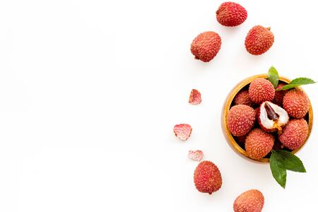 Fresh ripe lychee in bowl on white desk top-down frame copy space