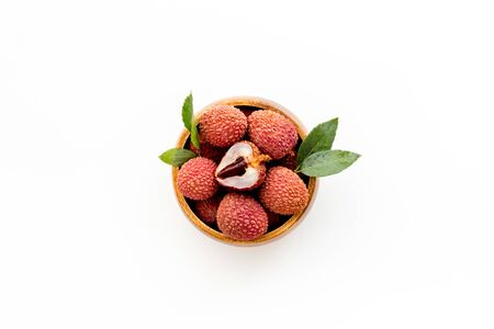 Ripe lychee. Exotic asian fruits in bowl on white desk top-down copy space