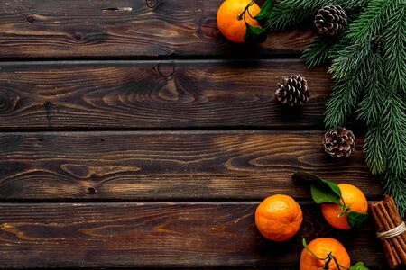 Tangerines near fir branches. New Year composition on dark wooden background top-down frame copy space