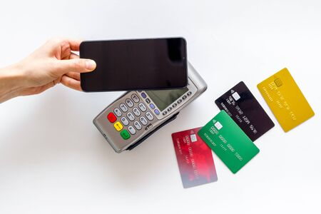 Contactless payment, NFC technology. Hand hold phone near terminal on white background top-down