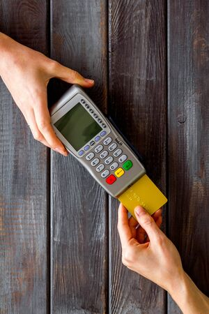 Payments in shops. Hand insert bank card in terminal on dark wooden background top-down.