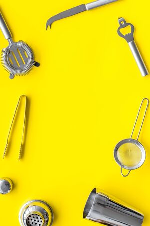 Bar utensil, tools - shaker, stainer - on yellow background top-down frame copy space