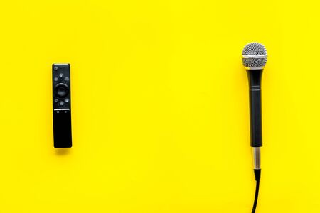 TV news concept. TV remote and microphone on yellow background top-down.