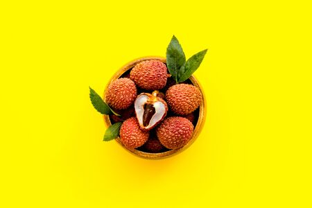 Lychee. Exotic asian fruits in bowl on yellow desk top-down copy space