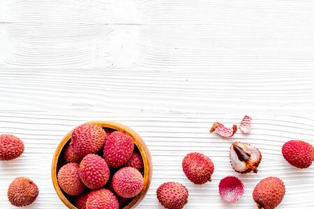 Fresh ripe lychee in bowl on white wooden desk top-down frame copy space