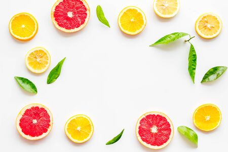 Citrus fruits - lemons, grapefruit slices - on white mockup, frame top-down.