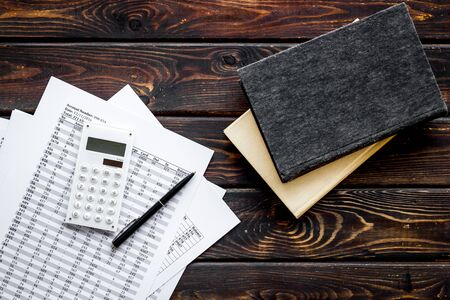 Financial literature. Books near documents, calculator on dark wooden background top-down.
