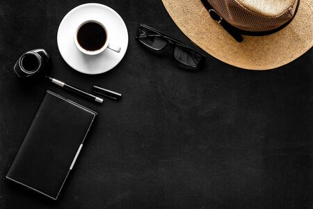 Bloggers work desk with hat and notebook on black background top-down copy space