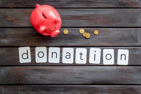 Donation concept. Piggy bank and coins on dark wooden background top-down