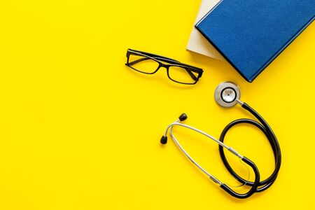 Medical books near stethoscope on yellow background top-down copy space