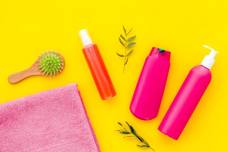 Hair care set with shampoo and towel - pink - on yellow background top-down.