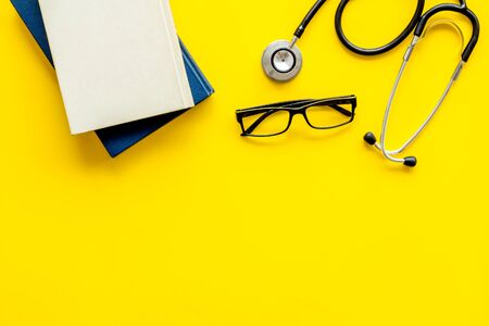 Medical books near stethoscope on yellow background top-down copy space Stock Photo - 140362021
