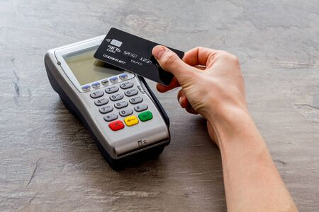 Contactless payment, paypass. Hand hold bank card near terminal on grey stone background