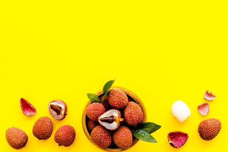 Fresh ripe lychee in bowl on yellow desk top-down frame copy space