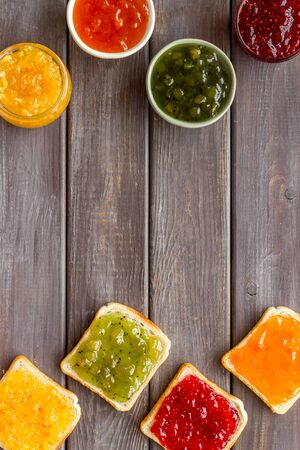 Toast with colorful fruit jam frame on dark wooden background.