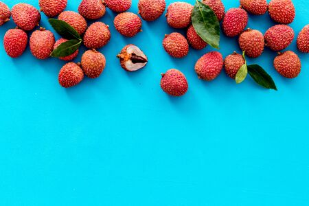 Lychee frame. Exotic asian fruits on blue background top-down.