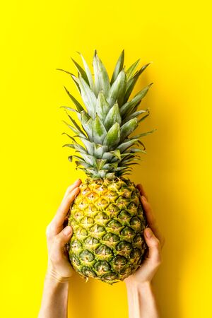 Pineapple in hands on bright yellow background top-down. Фото со стока
