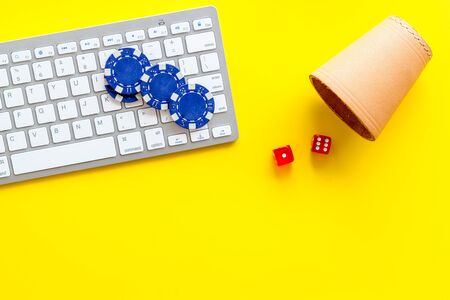Hazard gemes online concept. Poker chips, dices, cup for dice near keyboard on yellow background top-down.