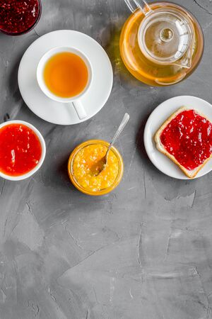 Tea party with jam. Toast, teapot, cup on grey background.