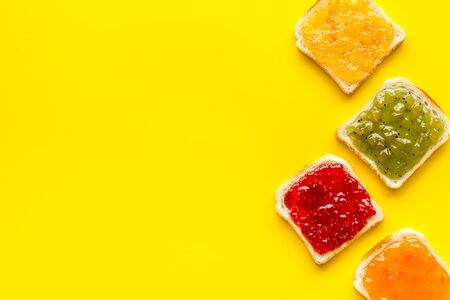 Toast with jam. Colorful set on yellow background top-down frame.