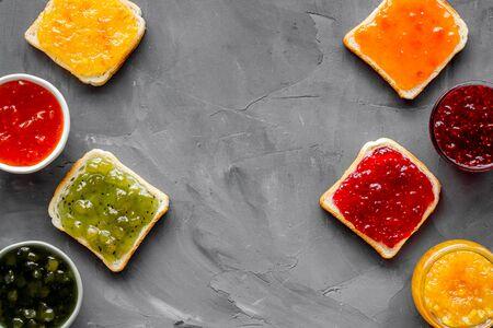 Toast with colorful fruit jam frame on grey background.