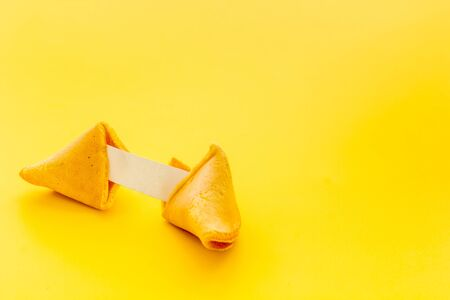 Fortune cookie cracked with blank slip on yellow background copy space Imagens