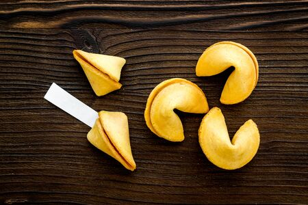 Fortune cookie with blank slip background on wooden table top-down Imagens