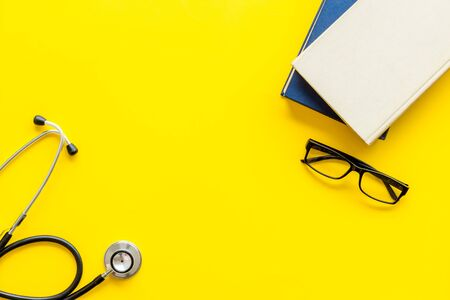 Medical books near stethoscope on yellow background top-down.