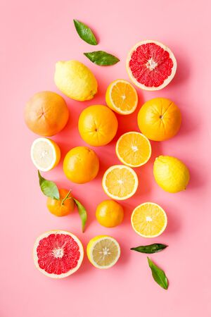 Fresh citrus background. Oranges, grapefruits, leaves - whole fruits and halfs - on pink background top-down.