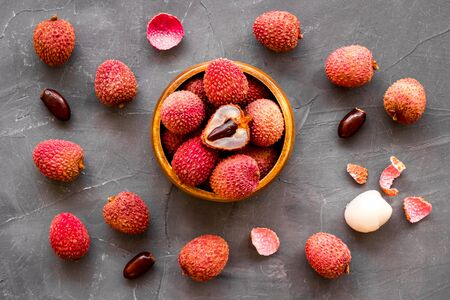 Ripe lychee. Exotic asian fruits in bowl on greydesk top-down.