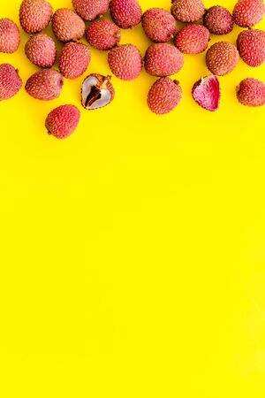 Lychee frame. Fresh juicy fruits on yellow background top-down.