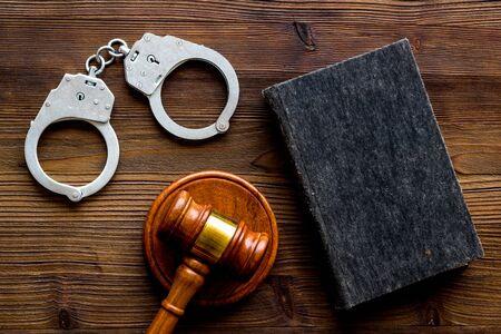 Arrest concept. Handcuffs near judge gavel on dark wooden background top-down. Imagens