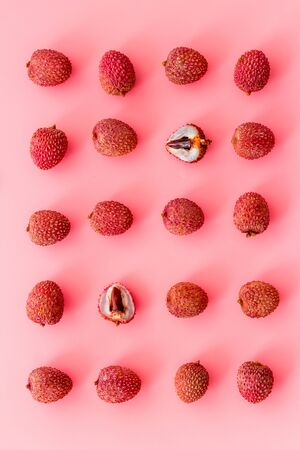 Lychee fruits pattern on pink background flat lay top-down.