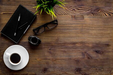 Writing concept with notebook on dark wooden background top-down copy space