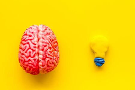 Brainstorm concept. Brain and bulb on yellow background top-down.