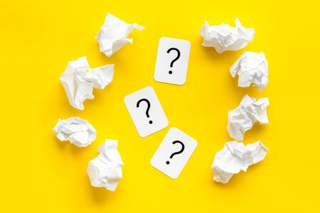 Writers block concept. Question mark among crumpled paper on yellow background top-down