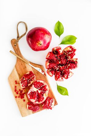 Peel pomegranate. Open fruit on cutting board on white background top-down.