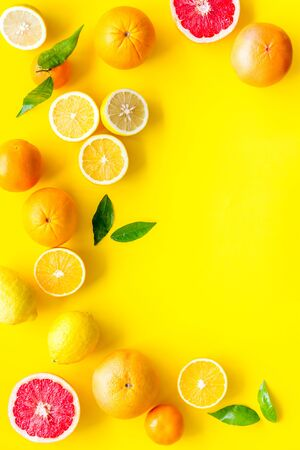 Fresh citrus frame. Oranges, tangerines, grapefruits, leaves on yellow background top-down.
