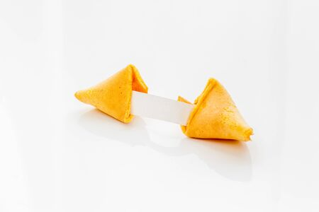 Fortune cookie cracked with blank slip on white background copy space
