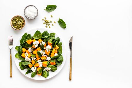 Healthy food concept. Salad with pumpkin and basil on white background top-down.
